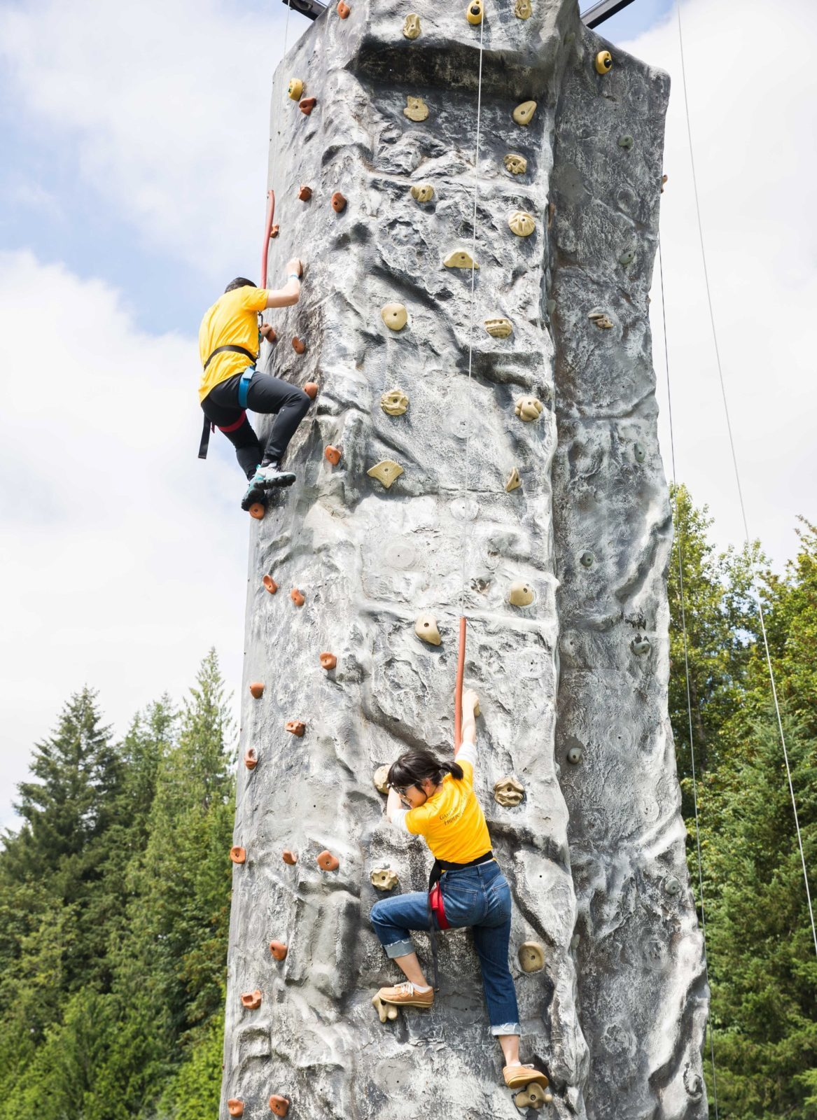 employees climbing a 32-ft rock wall at a company party